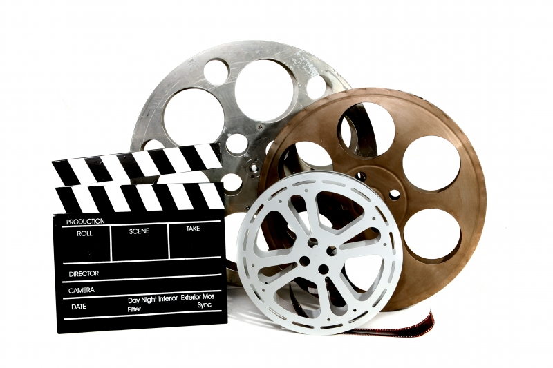 movie-production-clapper-and-film-tins-on-white